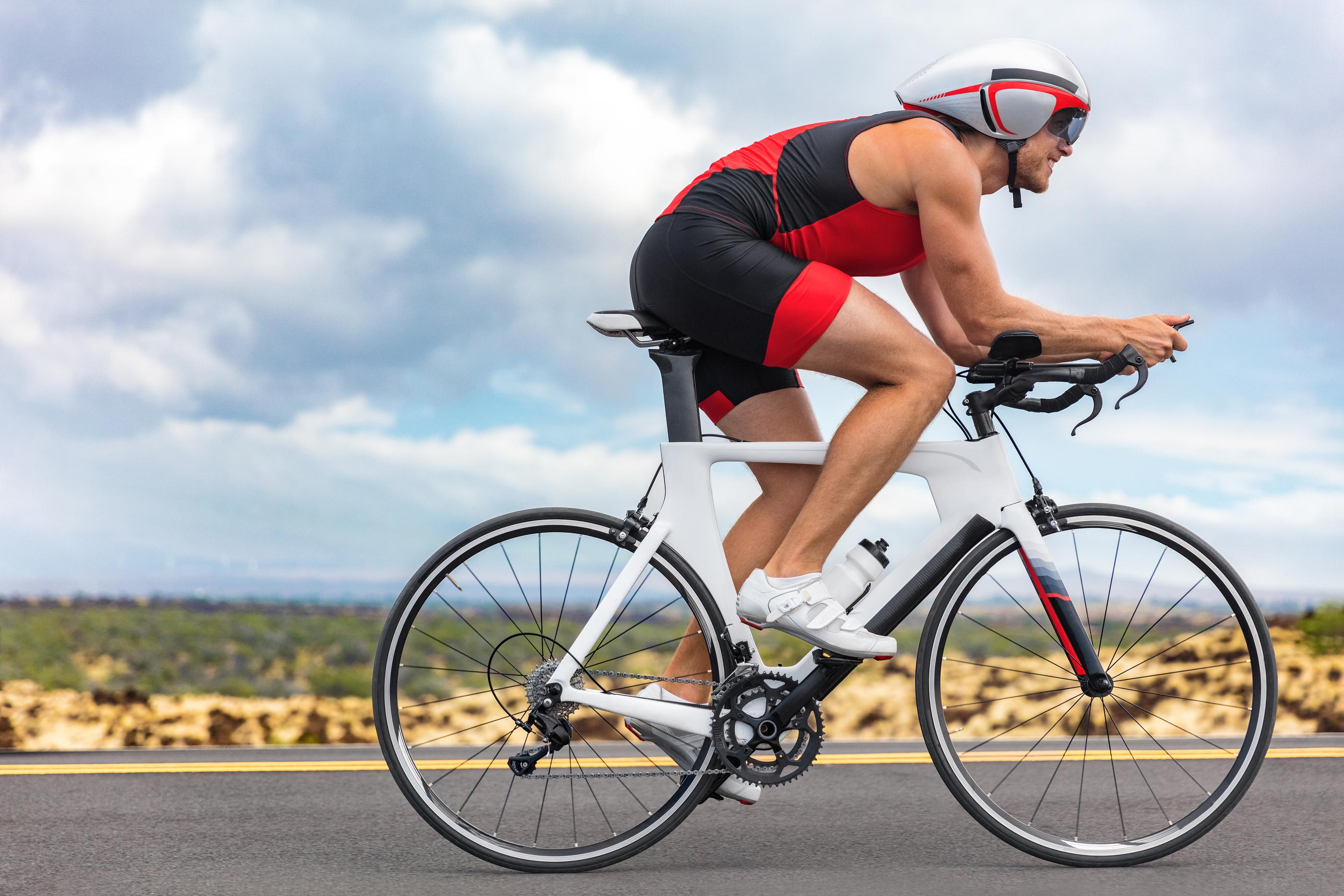 Cycling sport athlete man biking on triathlon bike. Fit male cyc